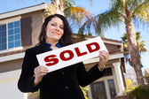 Woman Holding Sold Sign In Front of Home — Stock Photo