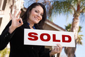 House and Woman Holding Sold Sign — Stock Photo