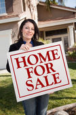 Hispanic Woman Holds Home For Sale Sign — Stock Photo