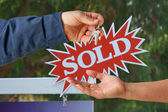 Handing Over the Keys and Sold Real Estate Sign — Stock Photo