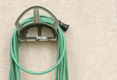 Garden Hose Hanging on Stucco Wall — Stock Photo