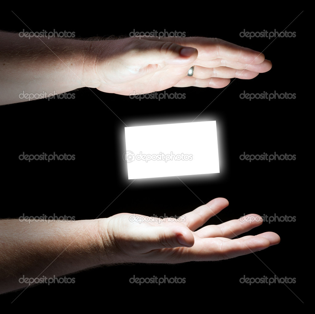 Glowing Hands on Black Background with Blank Business Card Floating in Between Ready for Your Message.  Stock Photo #2350616