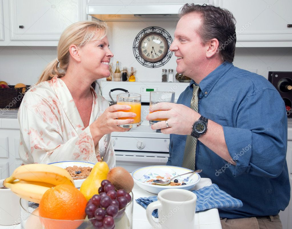 Happy Attractive Woman and Businessman In Kitchen with their Orange Juice and Breakfast.  Stock Photo #2354337