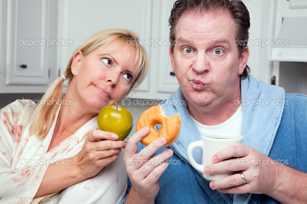 Couple in Kitchen Eating Donuts and Coffee or Healthy Fruit. — Stock Photo #2354550