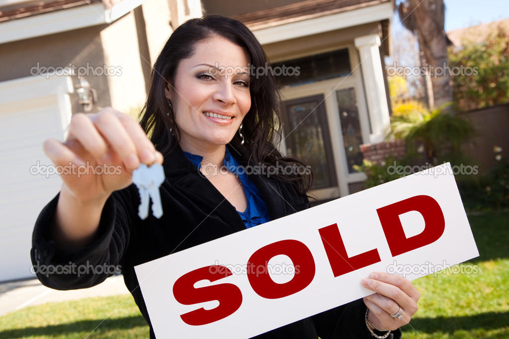 Happy Attractive Hispanic Woman Holding Keys and Sold Sign In Front of House. — Stock Photo #2358454