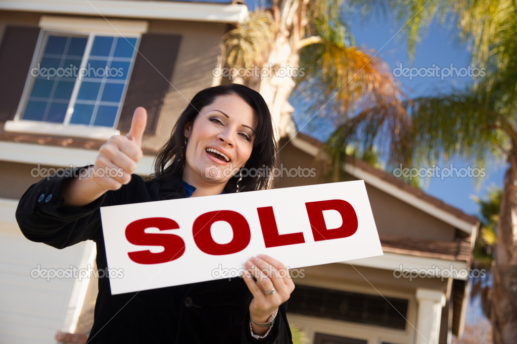 Happy Attractive Hispanic Woman with Thumbs Up Holding Sold Sign In Front of House. — Stock Photo #2358583