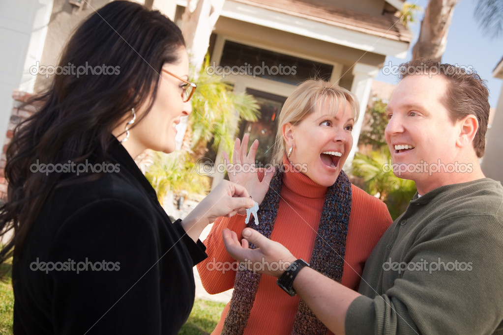 Hispanic Female Real Estate Agent Handing Over New House Keys to Excited Couple. — Stock Photo #2358688