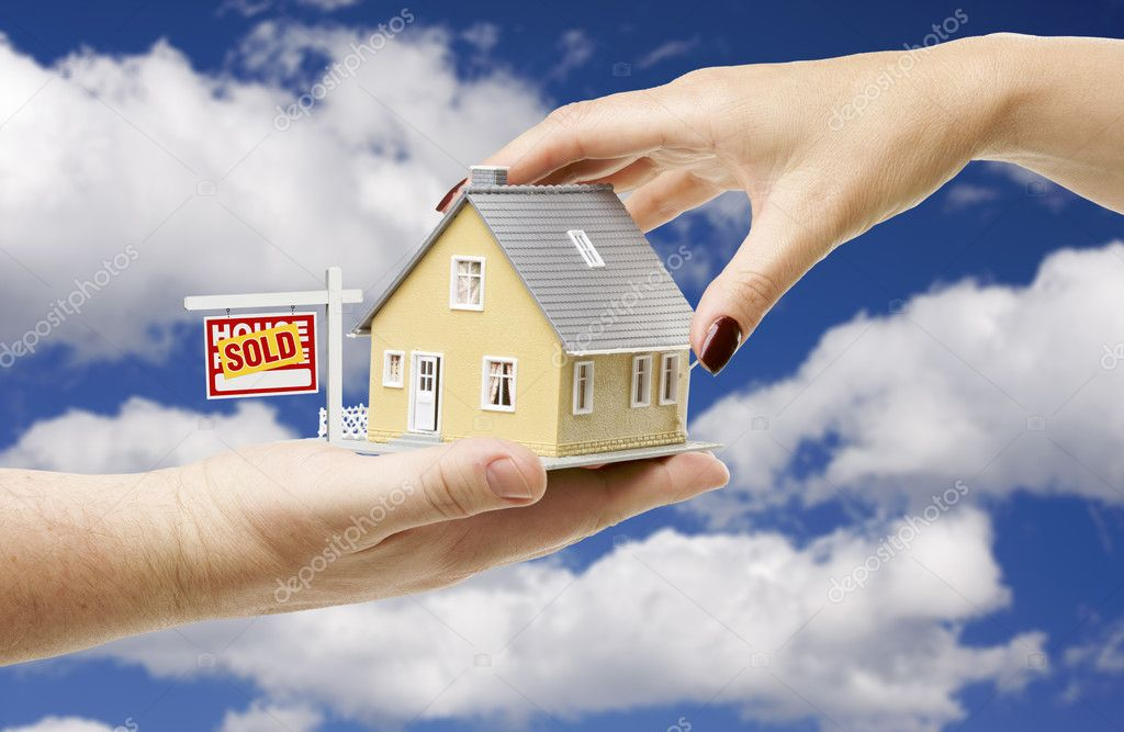 Reaching For A Home with Sold Real Estate Sign on a Bright Blue Cloudy Sky Background. — Stock Photo #2359238