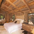Luxurious Rustic Log Cabin Bedroom - Stock Photo