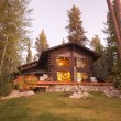 Beautiful Log Cabin Exterior Among Pines - Stock Photo