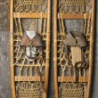 Antique Snowshoes on Rustic Cabin Wall - Stock Photo