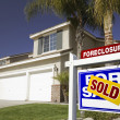 Blue Sold Foreclosure Sign and House - Stock Photo