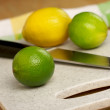 Limes, Lemons and Knife - Stock Photo