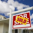 Sold Home For Sale Sign and New House - Stock Photo