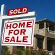 Stock Photo: Sold Home For Sale Sign and New House