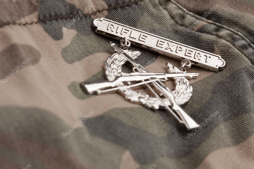 Rifle Expert War Medal on a Camouflage Material.  Stock Photo #2360795