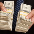Stock Photo: BusinessmHolding Stacks of Money