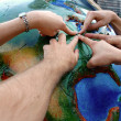 S fingers pointing at globe — Stock Photo