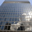 Stock Photo: Tall skyscraper with clouds reflections