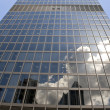 Tall skyscraper with clouds reflections — Stock Photo