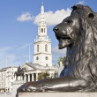 Statue of a lion in Trafalgar Square in London - Stock Photo
