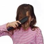 Beautiful girl combing her hair — Stock Photo