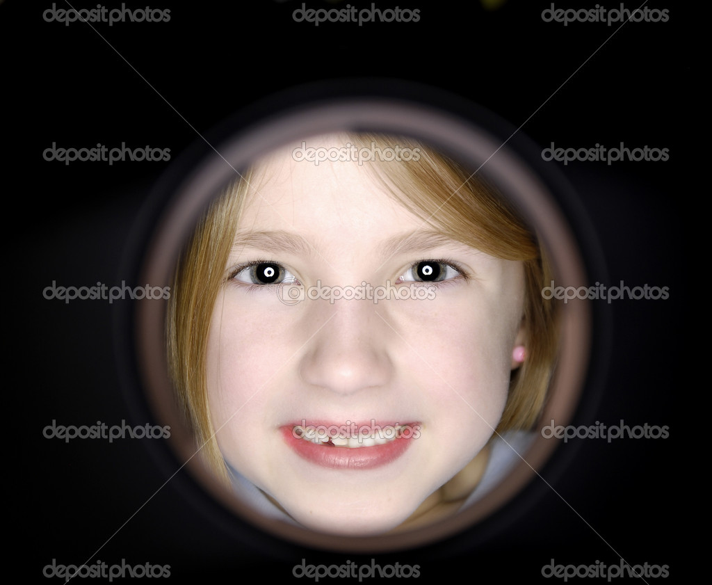 Little girl looking through hole with smile on face — Stock Photo #2343524