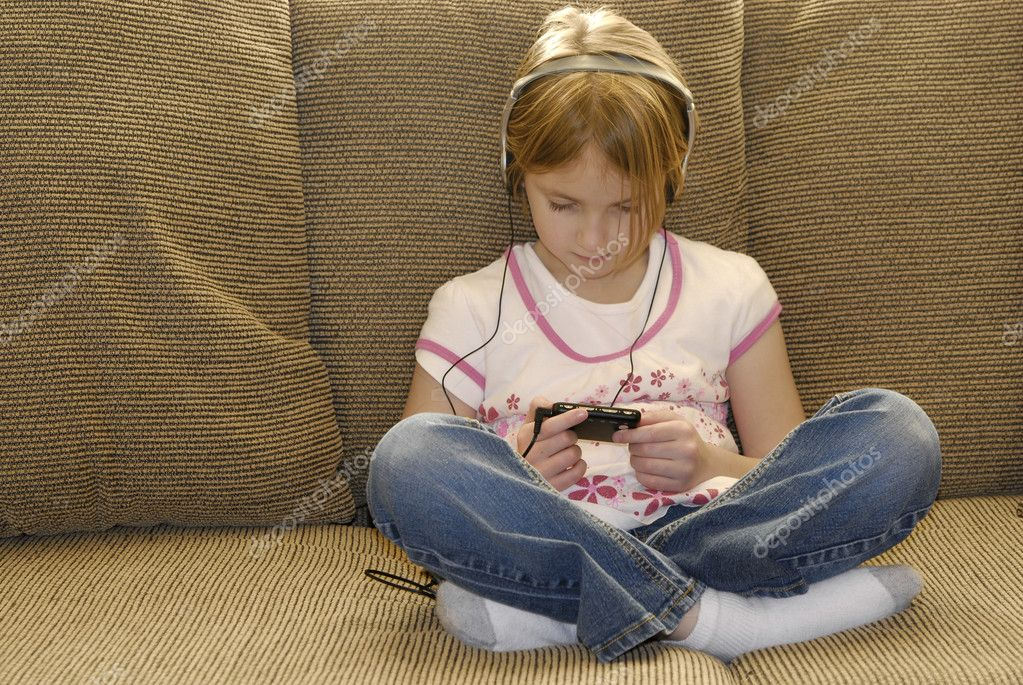 Little girl on couch listening to mp3 music with earphones  Stock Photo #2343839
