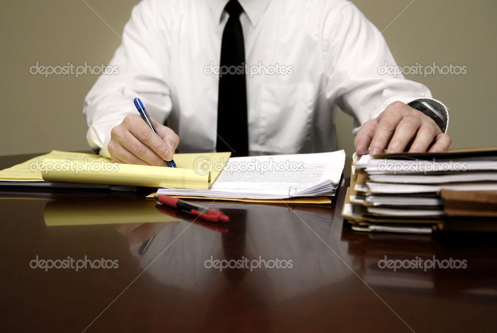 Business man sitting at desk holding pen with files — Stock Photo #2344271