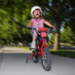 Royalty-Free Stock Photo: Little Girl Riding Fast on a Bike