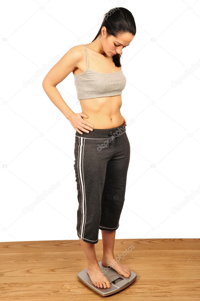 Young woman weighing herself on bathroom scales — Stock Photo #2456137