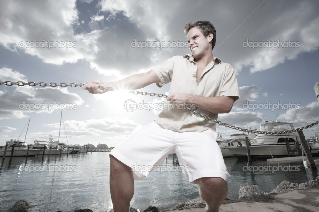Man pulling on a metal chain with the sunset in the background  — Stock Photo #2288913