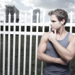 Royalty-Free Stock Photo: Man posing by a fence