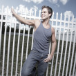 Man posing by a fence - Stock Photo