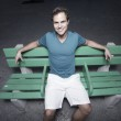 Man sitting on a bus bench — Stock Photo