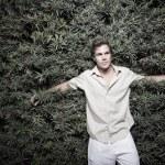 Man leaning back towards a bush — Stock Photo