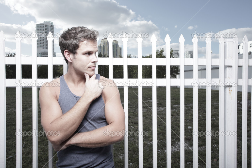Young man posing by a white fence on the street — Stock Photo #2330754