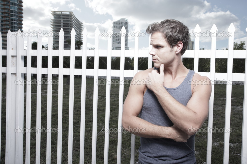 Young man posing by a white fence on the street — Stock Photo #2330755