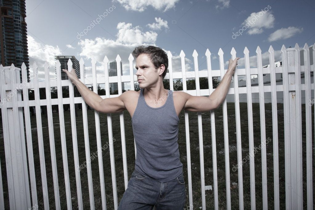 Young man posing by a white fence on the street — Stock Photo #2330763