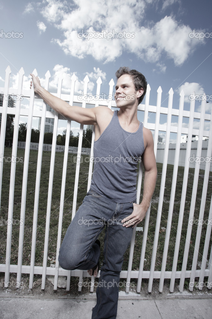 Young man posing by a white fence on the street — Stock Photo #2330772