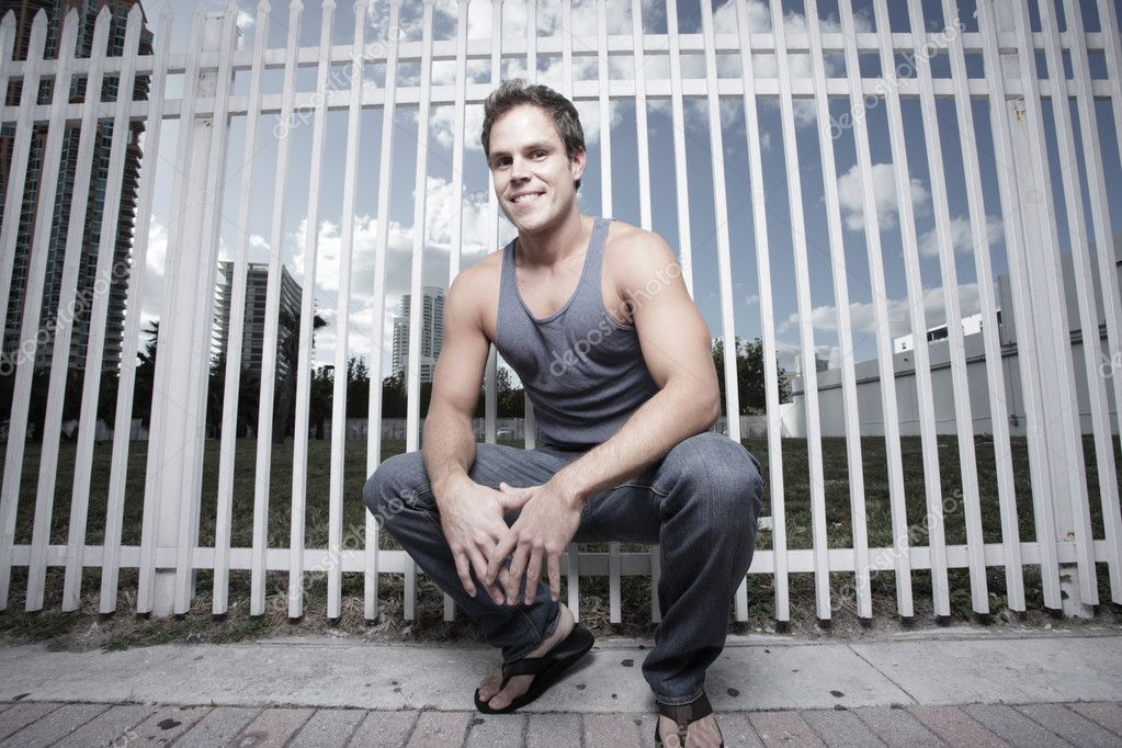 Young man squatting by a fence in the city — Stock Photo #2330777