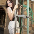 Woman climbing scaffolding — Stock Photo