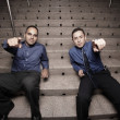 Businessmen sitting on stairs and pointing at the camera — Stock Photo