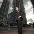 Ground angle view of a tall man with luxury high rises in the background — Stock Photo
