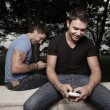 Happy men texting on their mobile phones — Stok fotoğraf