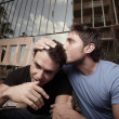 Man kissing his boyfriend on the head - Stock Photo