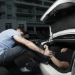 Man stuffing a dead body in his car trunk - Stock Photo