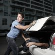 Stock Photo: Man hiding his murder victim in the trunk