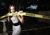 Woman tearing caution tape — Stock Photo