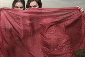 Mujeres detrás de un velo rojo — Foto de Stock